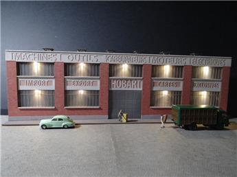 """Fond de décor en relief d´une usine avec baies éclairées """"Machines outils - Carburateurs"""""""