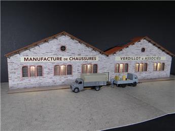 """Fond de décor en relief d´une usine avec baies éclairées """"Manufacture de chaussures"""""""